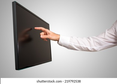 Man navigating a modern wall mounted high definition touch screen computer monitor with his finger , close up view of his arm and angled screen.