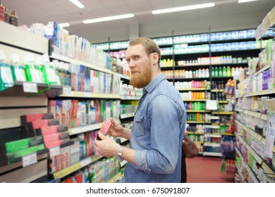 Man near  department with  care products  in   supermarket