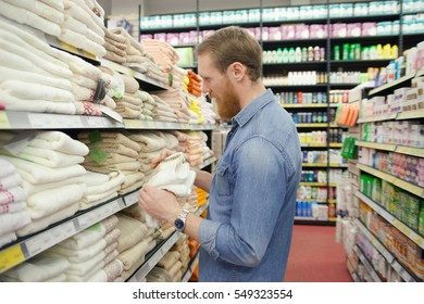 Man near  department with towels in   supermarket products for   home.