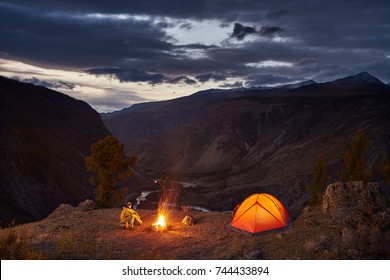 A man near tent glows and campfire at edge of mountains opposite valley after sunset.