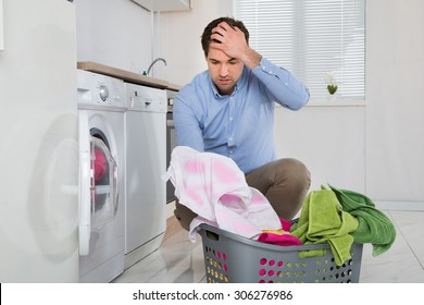 Man Near The Washing Machine With Laundry Basket Holding Stained Cloth In Kitchen