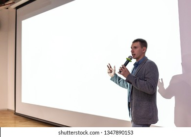 A man near the white screen of the projector with a micraphone talks about the project.