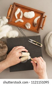 Man needle felting a wild rabbit with sheep wool
