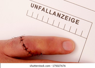 Man with needled finger fills out a accident report