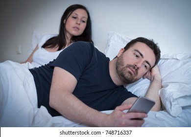 Man neglecting his girlfriend and using his mobile phone in the bed