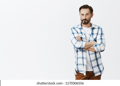 Man nervously listening to wife wanting confess in something. Intense worried serious-looking mature masculine male with beard, holding hands crossed, pursing lips and staring seriously at camera