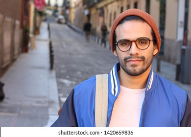 Man with a neutral expression outdoors
