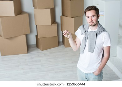 Man in a new house holds the keys on the background of boxes. Moving or housewarming.