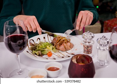 The man in the New Year's Eve is sitting in the restaurant for Serving a festive table near the Christmas tree. Celebrate the new year, it is fun, drinking wine and eating steak