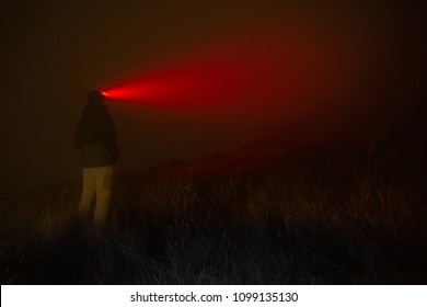 A man in the night fog lighting up with the faint light of his red lantern on his head.