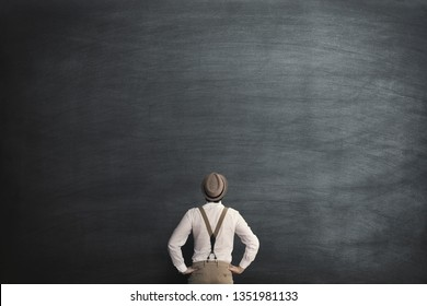 man with no ideas in front of empty blackboard
