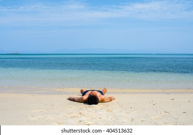 Man with no shirt lay down on the beach