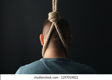 Man with noose around neck on dark background. Suicide awareness concept