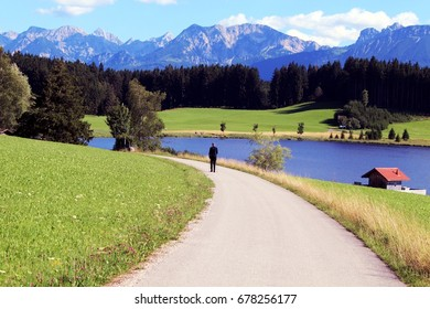 Man, Nordic Walking, at a pond in front of the Mountains
