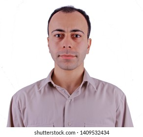 Man in normal shirt looking at camera while standing against gray background with normal facial expression. Man takes pictures for passport in local studio
