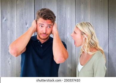 Man not listening to his shouting girlfriend against wooden planks