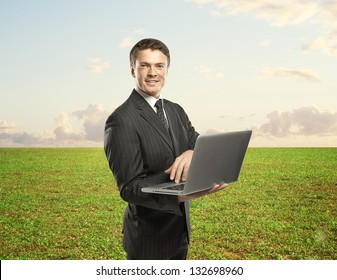 man with notebook standing on green field