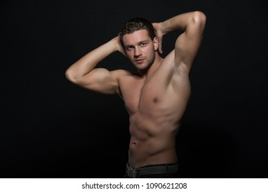 Man with nude muscular torso put hands behind head posing. Macho with muscular chest looks attractive, black background copy space. Athelete with sporty figure on confident face. Muscul power concept.
