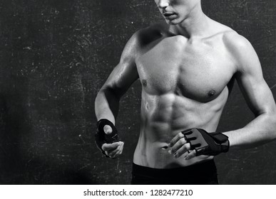 A man with a nude pumped body athlete in gloves sports fitness