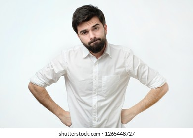 Man is offended because his girlfriend forgot about his birthday. Annoyed and angry funny mature caucasian man with beard, frowning and sulking from disappointment, holding hands on hips
