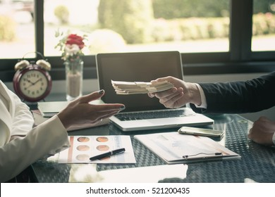 Man offering batch of hundred dollar bills. Hands close up. Venality, bribe, corruption concept. Hand giving money - United States Dollars (or USD). Hand receiving money from businessman.