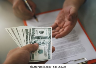 Man offering batch of hundred dollar bills. Close up of business man signing contract making a deal, business contract details.