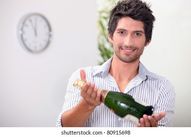 Man offering a bottle of champagne at five minutes to midnight