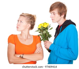 man offering flowers to his girlfriend who is very upset after argument