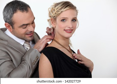 man offering his girlfriend a necklace