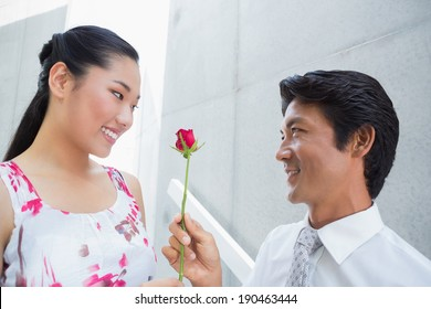 Man offering a red rose to girlfriend on the stairs
