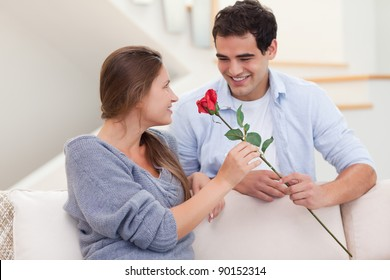 Man offering a rose to his girlfriend in their living room