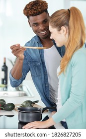 man offering sppon to his girlfriend to taste the food