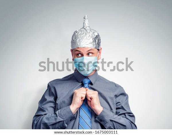 Mann in Bürokleidung, auf seinem Kopf eine Kappe aus Aluminiumfolie auf seinem Gesicht, eine ärztliche Atemmaske. Aufmerktention-Corona-Virus-Konzept