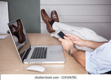 Man in office with feet on desk and laptop - landscape interior.