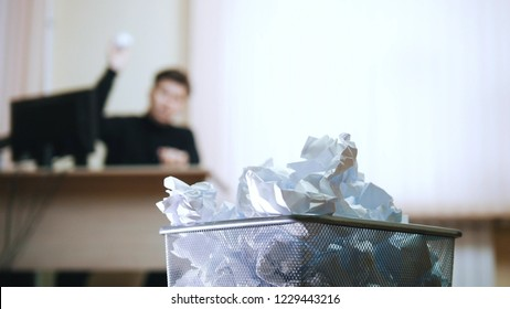 A man in office prepares to throw the paper into the trashcan