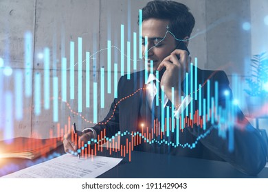 A man in office signing papers while talking phone and stock market graph and chart hologram. Double exposure. Formal wear.