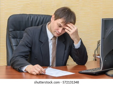 The man in the office thoughtfully looking into the document