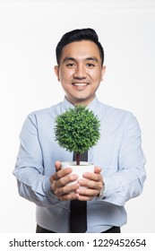Man in office wear holding a potted plant
