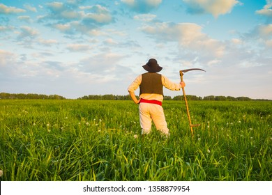 man in old clothes mows grass in the field
