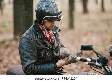 Man and old custom cafe-racer Motorcycle on forest