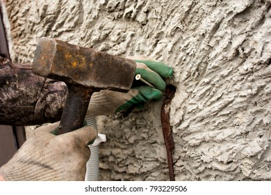 A man in old dirty gloves is working with a heavy sledgehammer.A man is working with a heavy hammer.