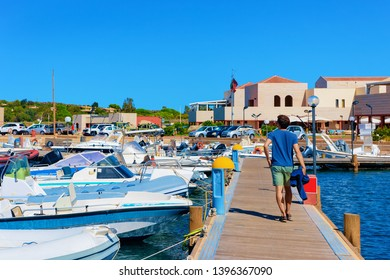 Man in Old Sardinian Port with ships at Mediterranean Sea in city of Villasimius in South Sardinia Island in Italy in summer. Cityscape with Yachts and boats