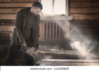 a man in an old wooden house dismantles the floors of logs with an electric saw