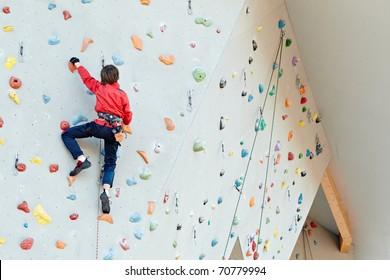 Man on artificial exercise climbing wall
