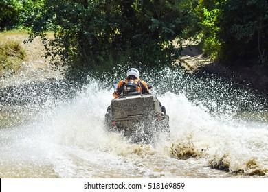 The man on the ATV crosses a stream. Tourist walks on a cross-country terrain.