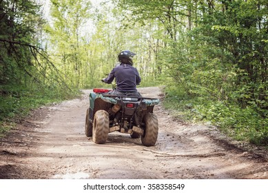 Man on the ATV Quad Bike on the mountains road.
