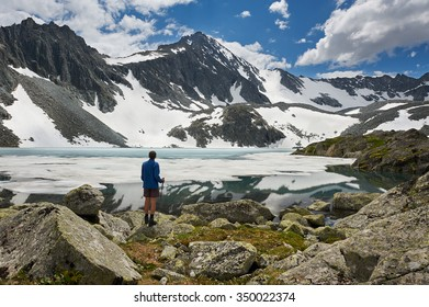 Man on the background of a mountain lake. Russia, Siberia, Altai mountains, Katun ridge.