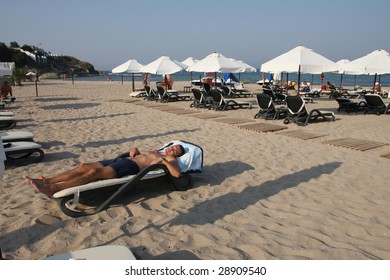 The man on the beach bed with his eyes closed. Relax. Sunset.