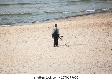 man on the beach with a metal detector