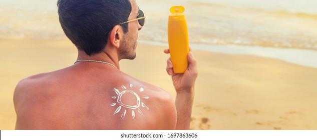 A man on the beach with sunscreen on his back. Selective focus.